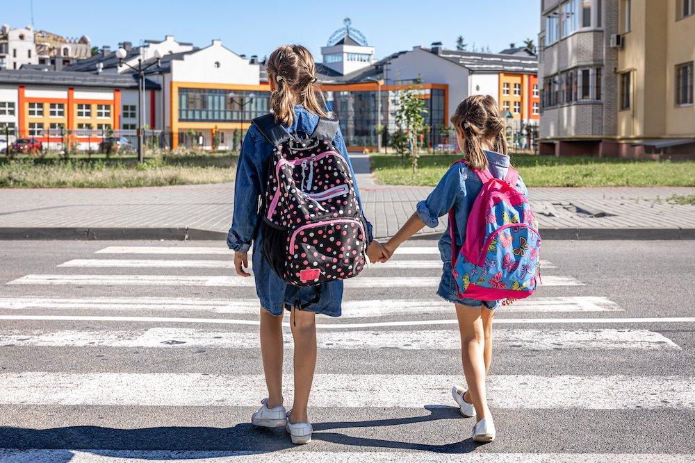 dwie dziewczynki z plecakami przechodza przez pasy w drodze do szkoły