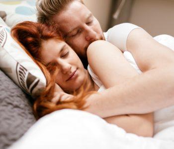 Para śpi w łóżku przytulona do siebie