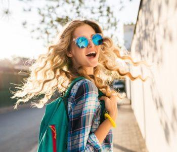 uśmiechnięta pani z plecakiem i w okularach słonecznych