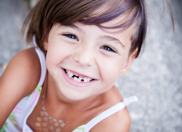 Little girl with big smile and missing milk teeth